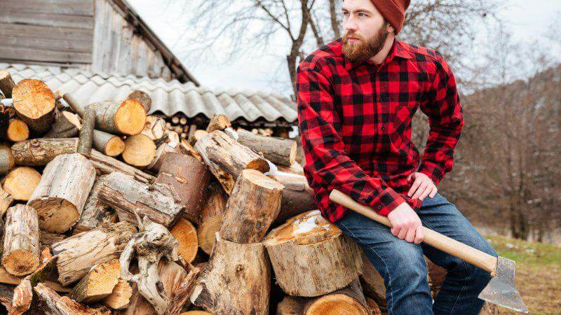 man with beard chopping wood outside